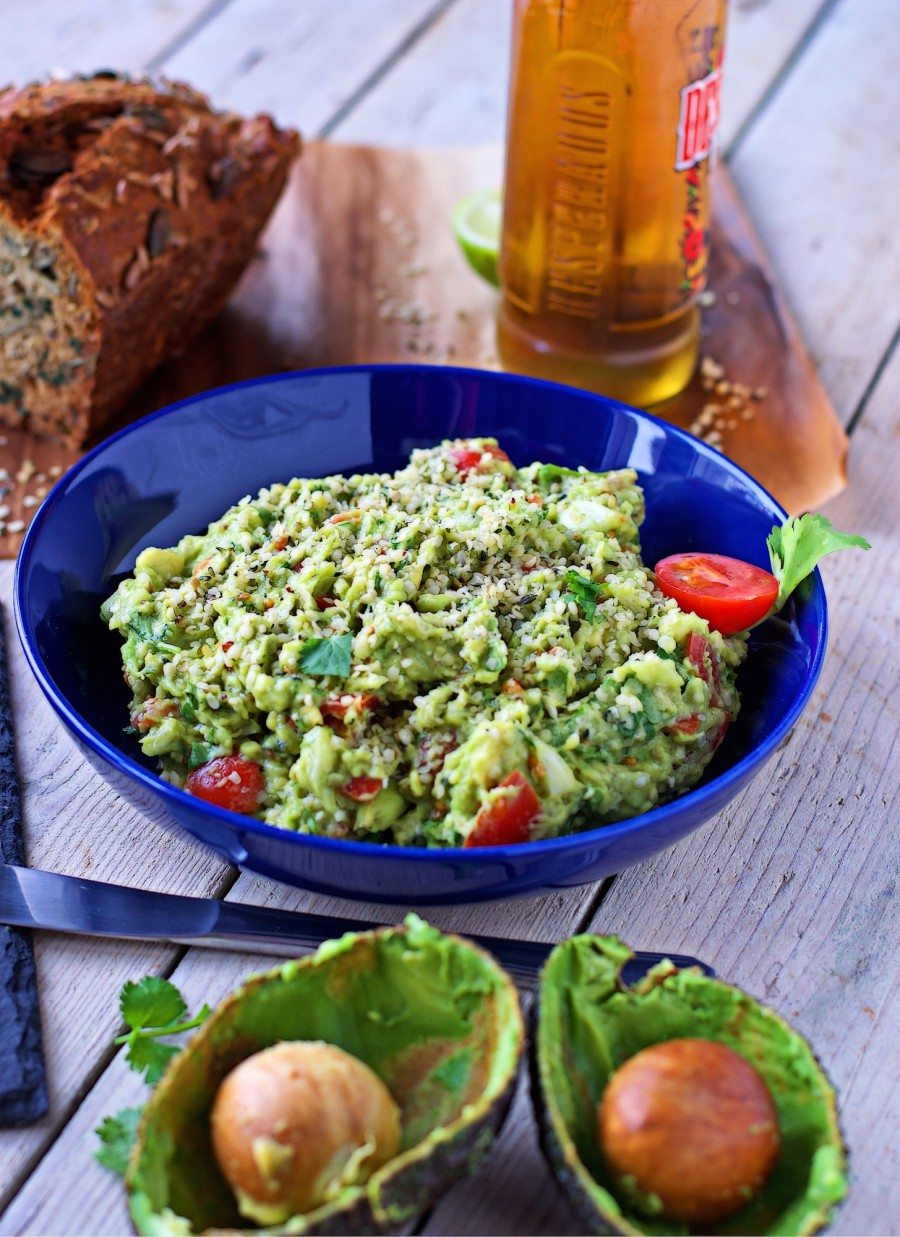 A large bowl full of the Hemp Guacamole with two empty avocado halves in the foreground.