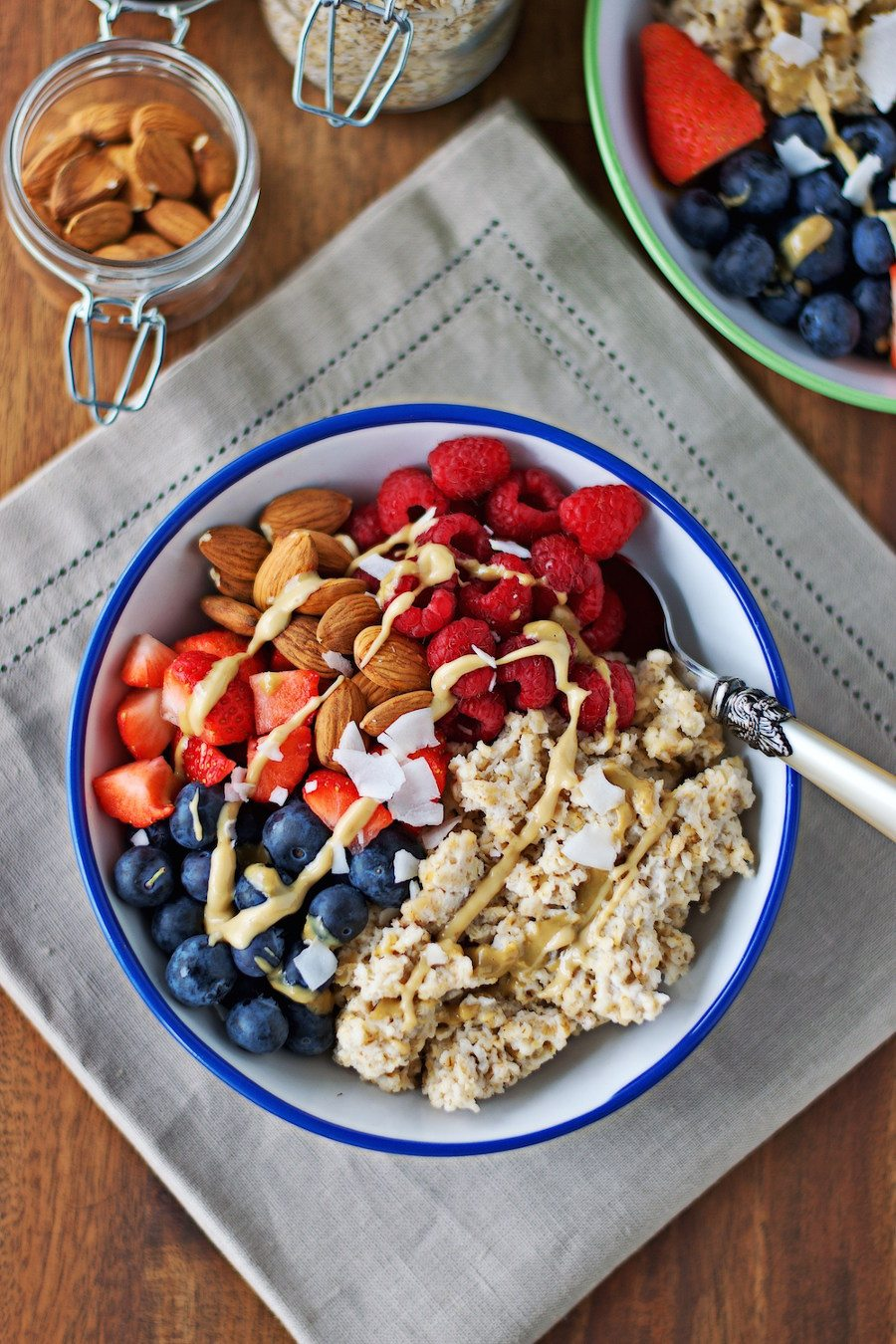 Top view of one Breakfast Bowl with fresh fruits and nuts, with a spoon at the side.