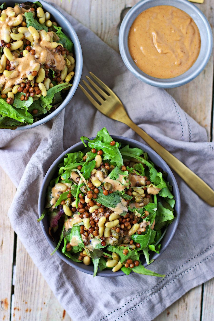 Two bowls of the high Protein Salad with a small bowl of dressing on the side.
