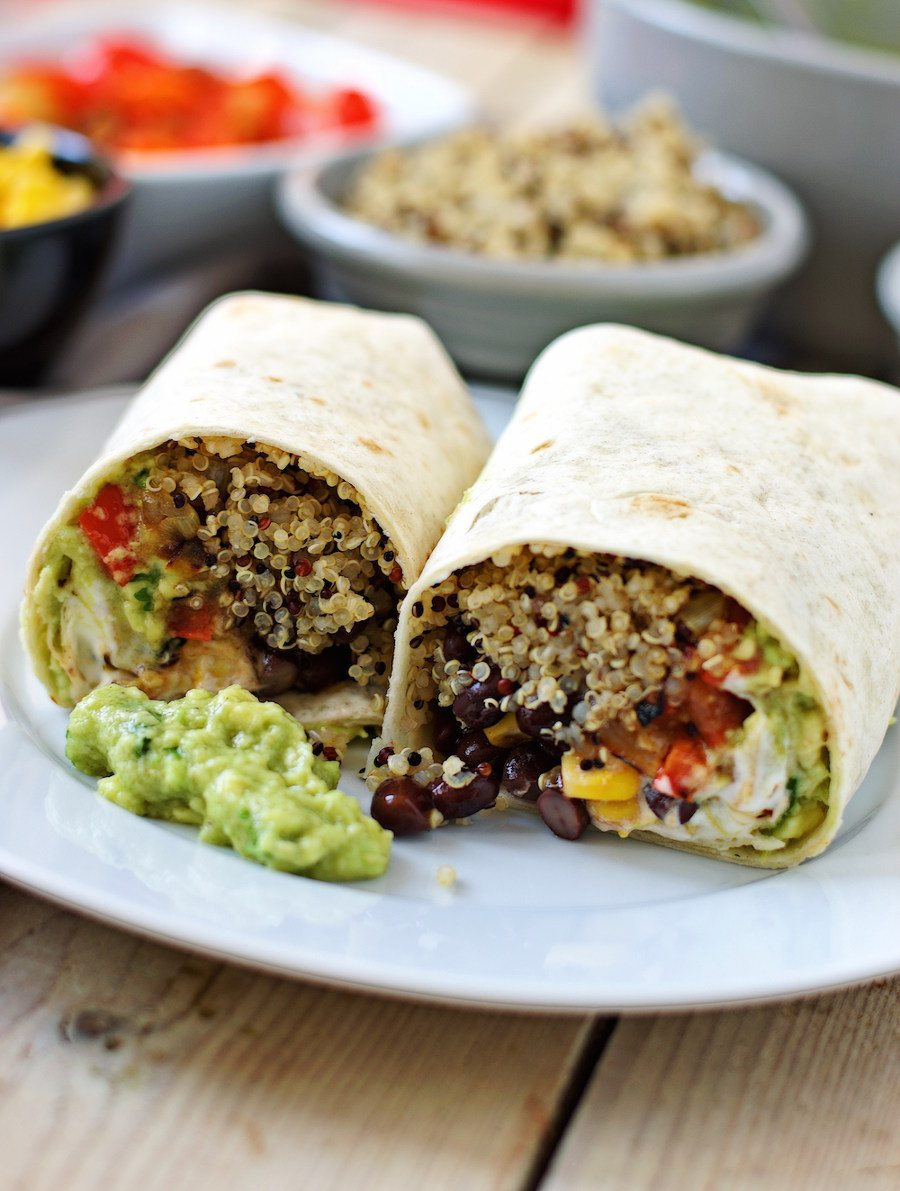 Two Mexican Quinoa Wrap halves side-by-side on the white plate with a spoon of guacamole.