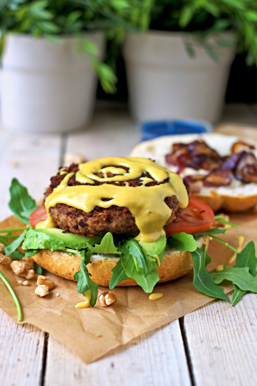 Side view on the open Vegan Lentil Burger with mustard sauce being sprinkled on the patty.