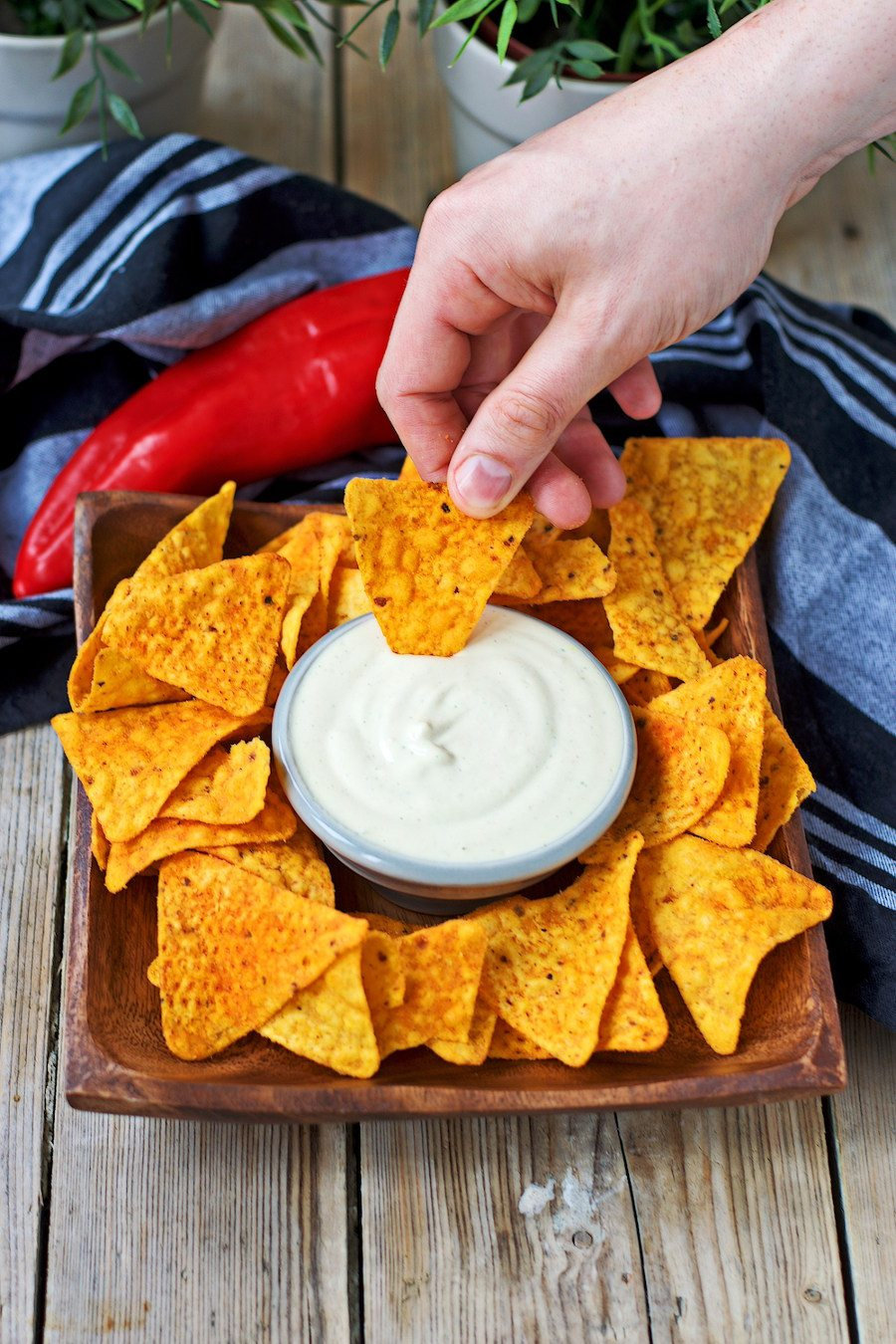 A small bowls with the Vegan Cheese Sauce is placed on a bed to tortilla chips.