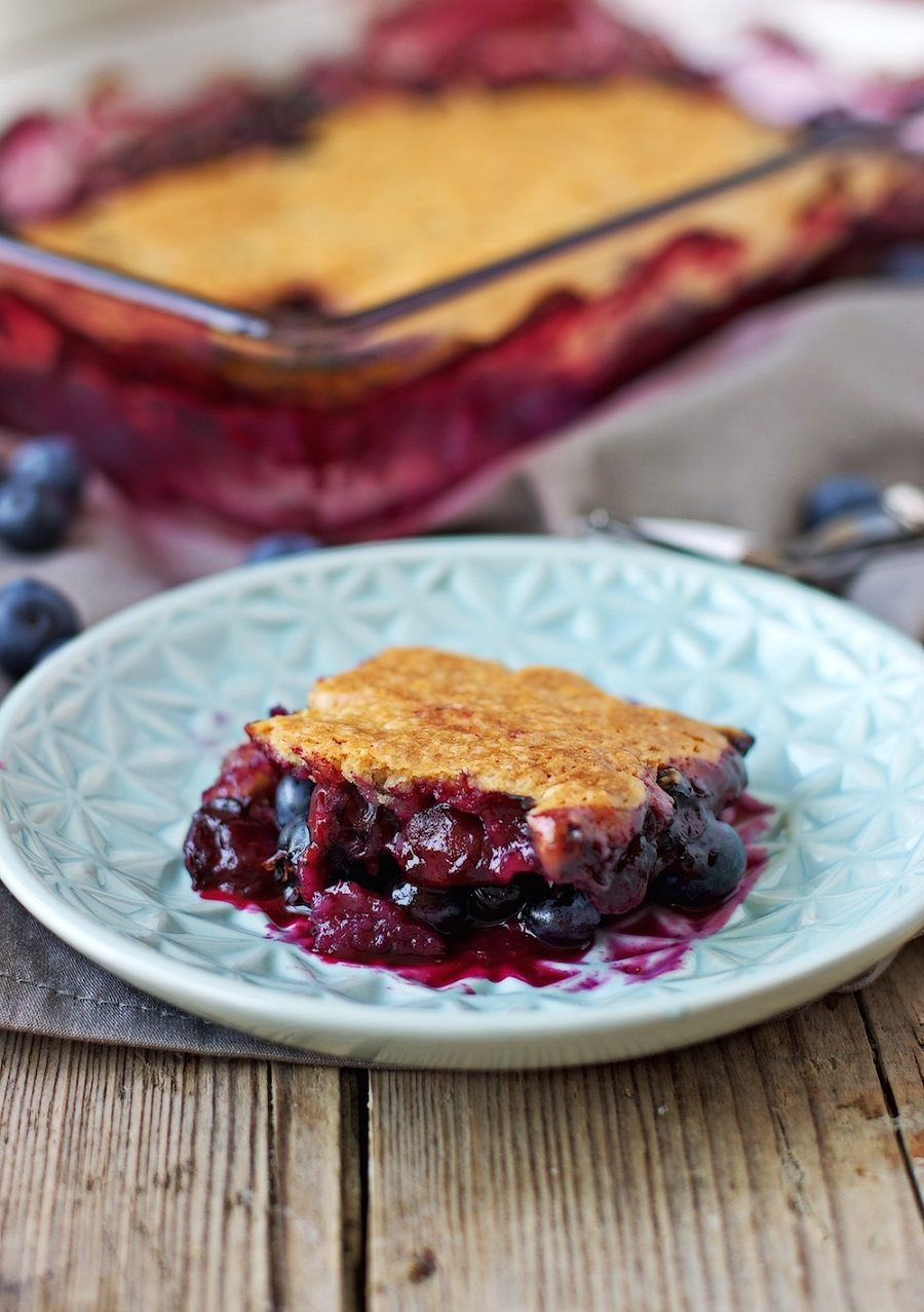 A single piece of the Easy Blueberry Cobbler is placed on a small blue plate, and seen from the side. | #vegan #glutenfree #dessert contentednesscooking.com