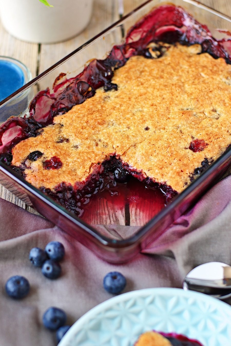 Closeup on the Easy Blueberry Cobbler in the casserole dish, showing the juicy fruit mix and crunchy top.