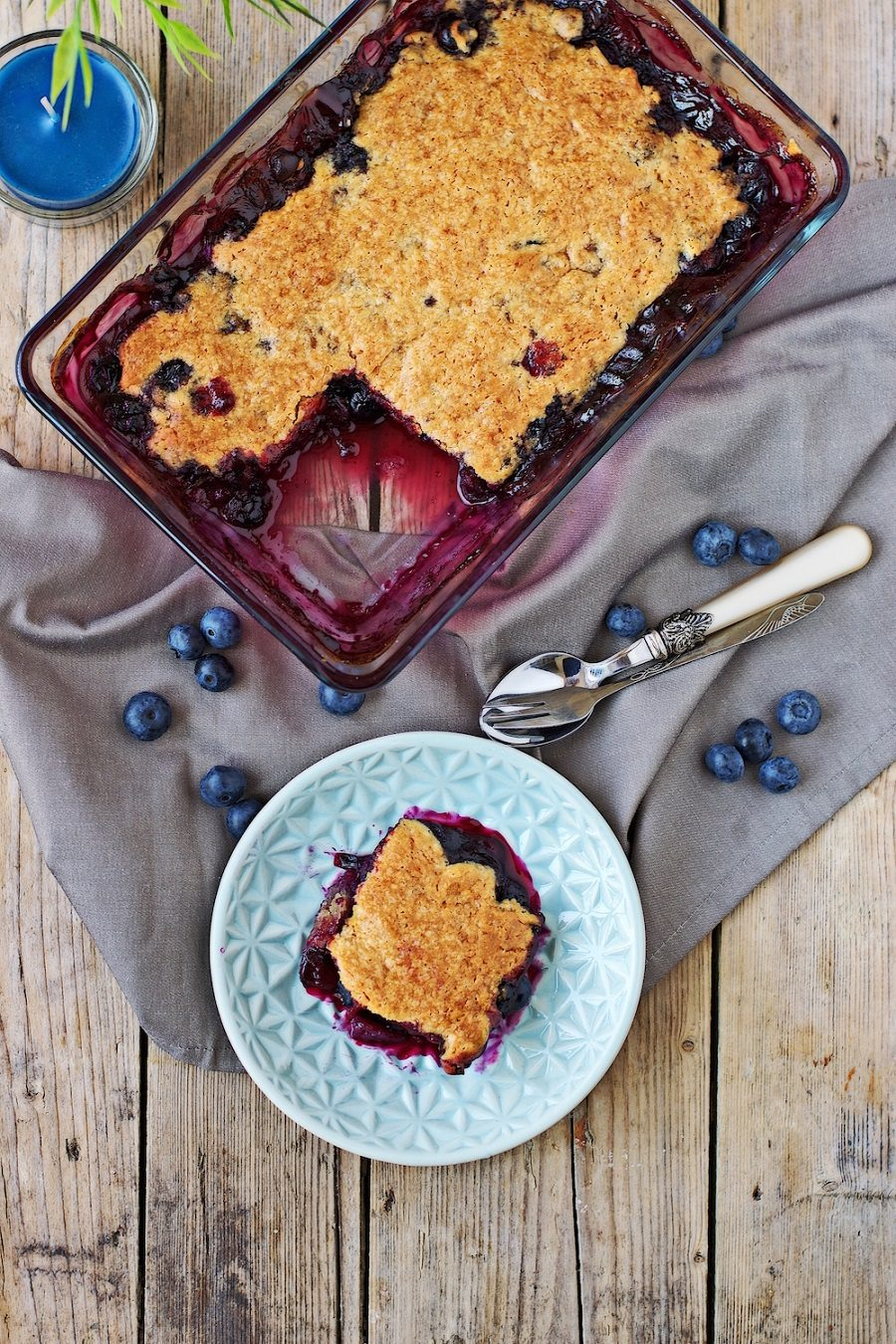 A glass casserole dish with the easy Easy Blueberry Cobbler seen from above, a portion is taken out and on a small plate.