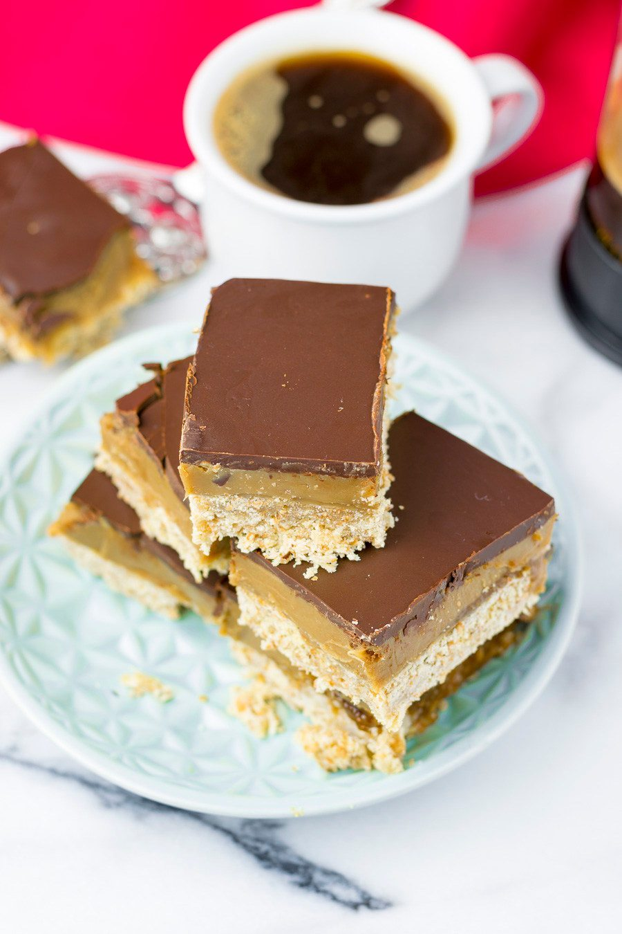 Top view on the caramel shortbread, showing the chocolate top, a cup of coffee in the background.