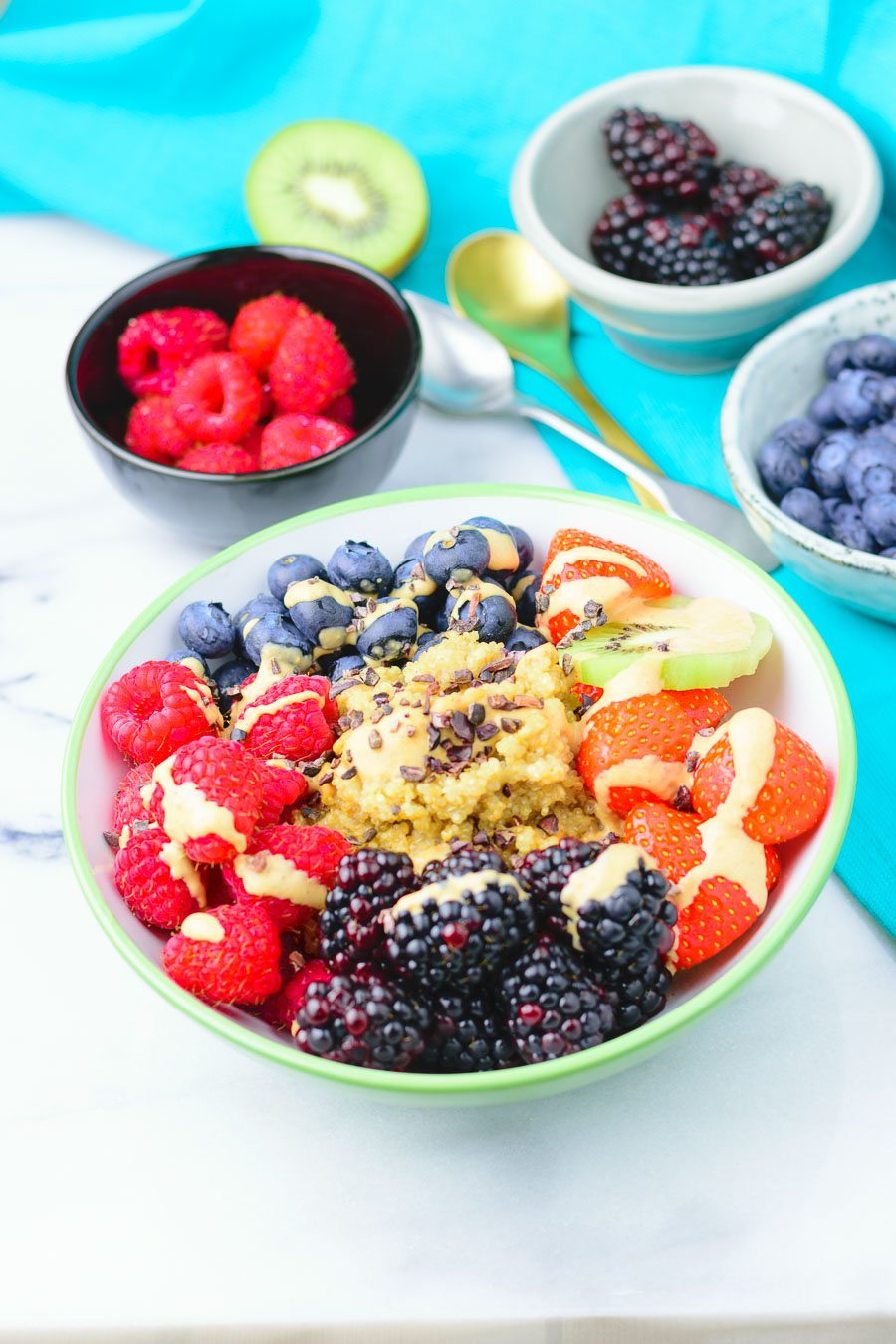 A single Quinoa Breakfast Bowl with all ingredients in sections and sprinkled with sauce.