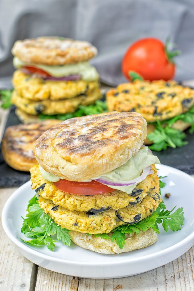 An assembled Mediterranean Vegan Burger with several more in the background.