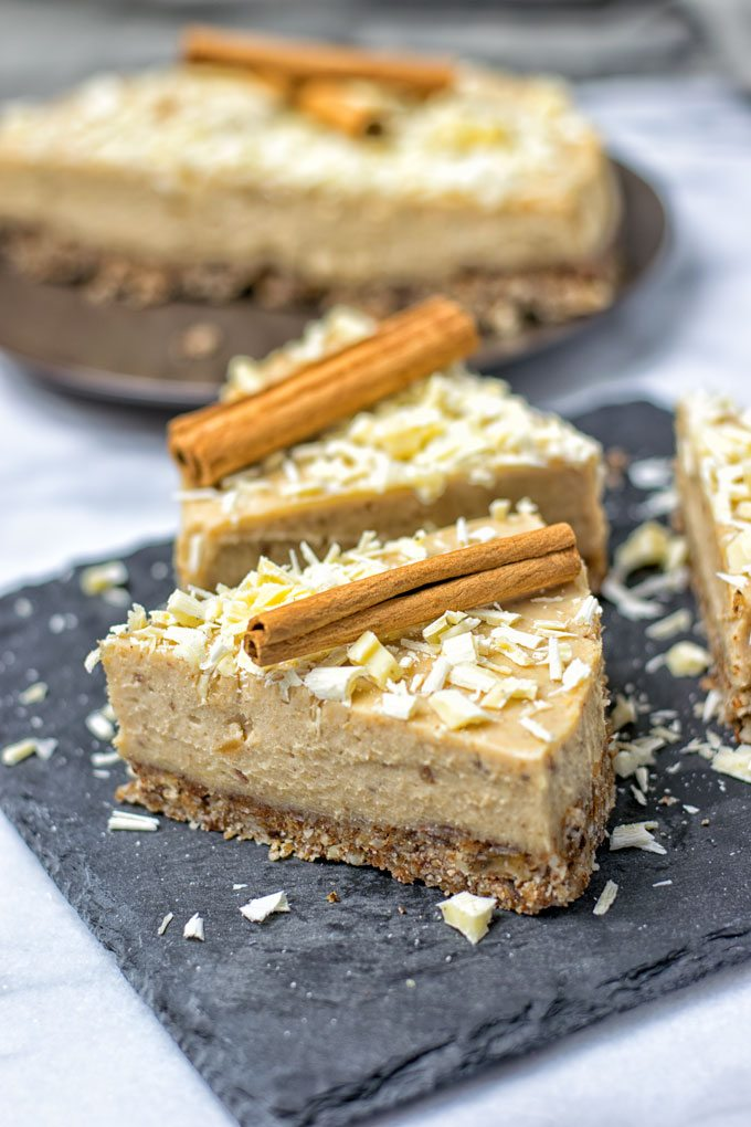 Several slices of the Cinnamon White Chocolate Cheesecake on serving plates.
