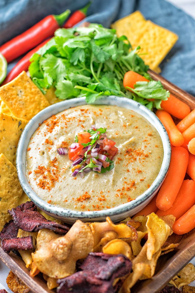 Bowl of the Mexican Cheese Dip served with fresh vegetables and veggie chips.