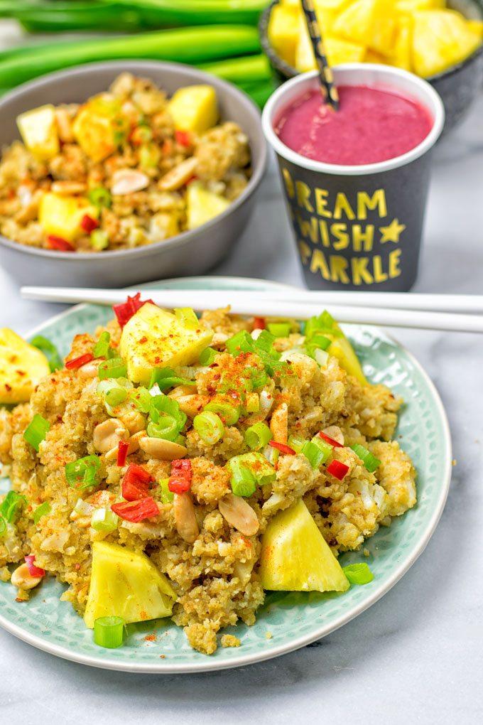 Closeup on a plate of Thai Green Curry Detox Cauliflower Rice with white chopsticks.