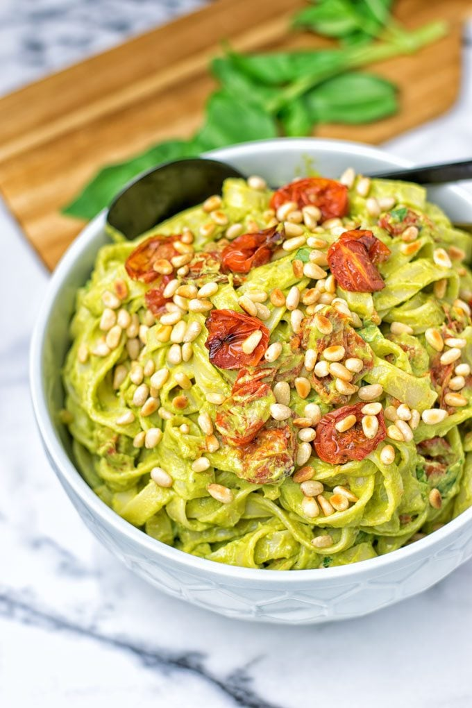 A bowl of pasta mixed with the Avocado Pesto Sauce garnished with sun-dried tomatoes and toasted pine nuts.