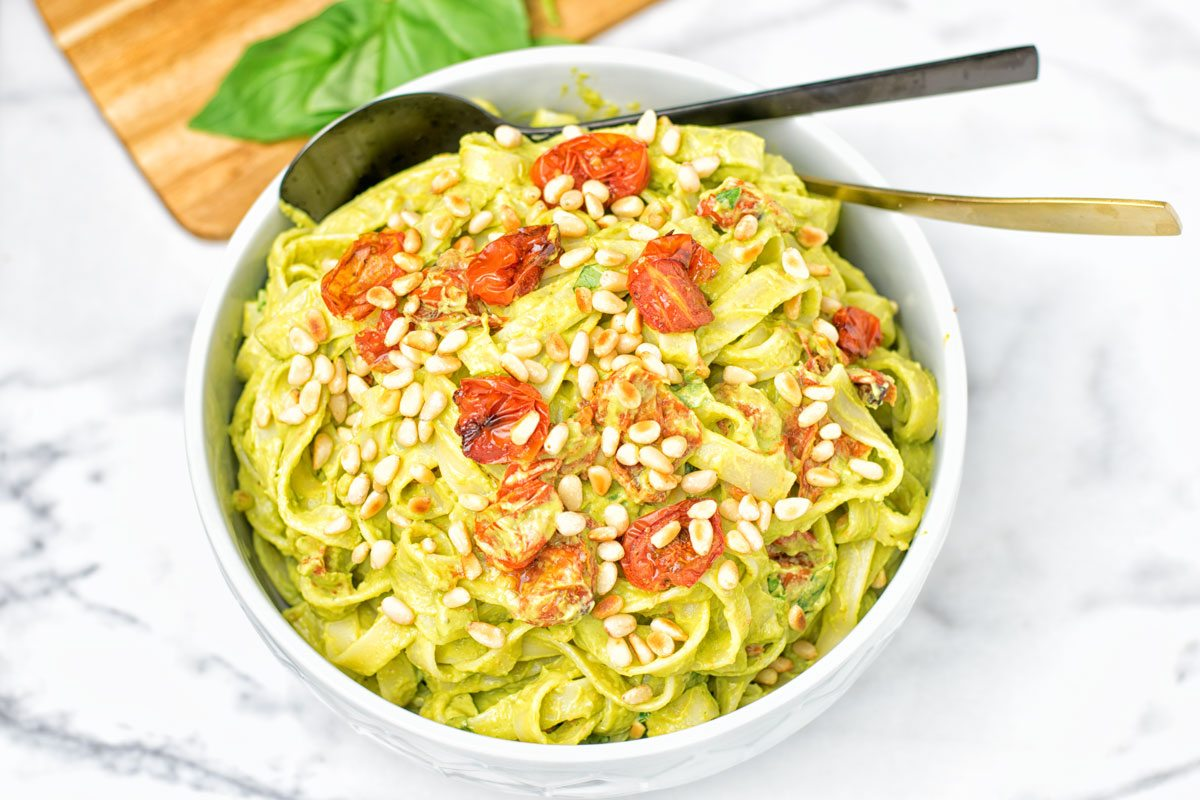A large bowl of Avocado Pesto Pasta with a black and golden spoon.