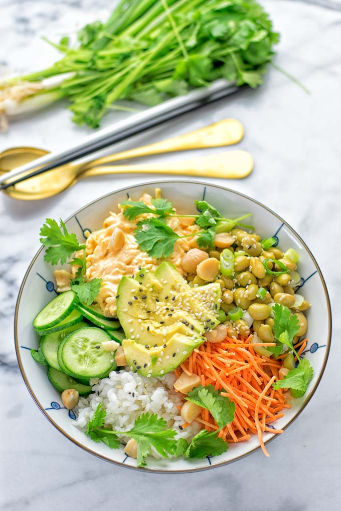 Easy and delicious: This Hawaiian Poke Bowl is naturally vegan, gluten free. Made with sushi rice, an amazing white cabbage mix with creamy sriracha sauce and edamame for protein richness. You can add options like shredded carrots, seaweed flakes, and more to build your dream bowl. Try it now and enjoy for lunch, dinner, meal prep! #vegan #glutenfree #vegetarian #dairyfree #contentednesscooking #dinner #lunch #pokebowl #hawaiianfood #easyfood #mealprep #budgetmeals #worklunchideas #bowlrecipes