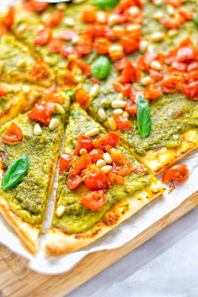 This White Bean and Pesto Pizza is super easy to make, entirely vegan and gluten free. If you love pizza and pesto you're coming to the right place. It's so delicious for lunch, dinner, meal preparation, and work lunch. Try it now and fall in love. #vegan #glutenfree #dairyfree #contentednesscooking #pesto #pizza #mealprep #worklunchideas #easyfood #lunch #dinner