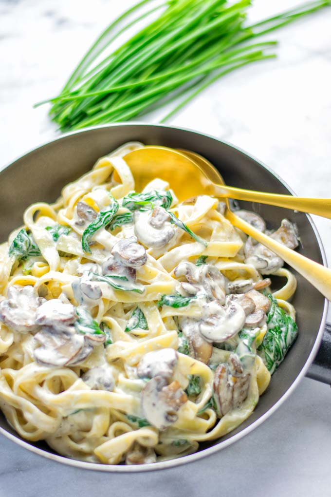 Super creamy and easy to make: Spinach Mushroom Fettuccine Alfredo entirely vegan, gluten free and the ultimate comfort food for dinner, lunch, meal preparation that the whole family will love. If you're looking for a delicious fettuccine Alfredo recipe try it now, it's a keeper. #vegan #glutenfree #dairyfree #vegetarian #contentednesscooking #dinner #lunch #mealprep #worklunchideas #fettuccinealfredo #spinachrecipes #mushroomrecipes #familydinnerideas #fettuccinerecipes #easy20minutemeals