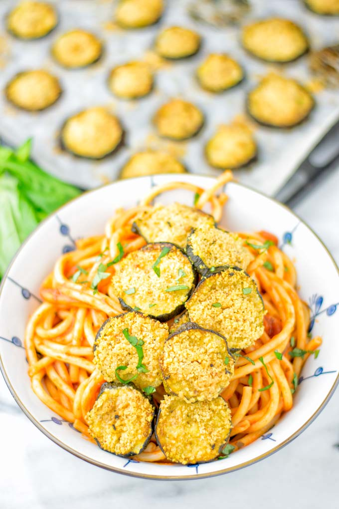 This Baked Zucchini Parmesan is entirely vegan, gluten free and will be a family favorite. Serve it with pasta, dips, as appetizer, dinner, lunches, meal preparation, or work lunch. Sprinkled with the best dairy free parmesan cheese that makes all the difference. Try it now. #vegan #dairyfree #vegetarian #contentednesscooking #dinner #lunch #mealprep #worklunchideas #zucchiniparmesan #zucchiniparmesanbaked #zucchiniparmesancrisps #comfortfood #kidfriendlydinners #familydinnerideas