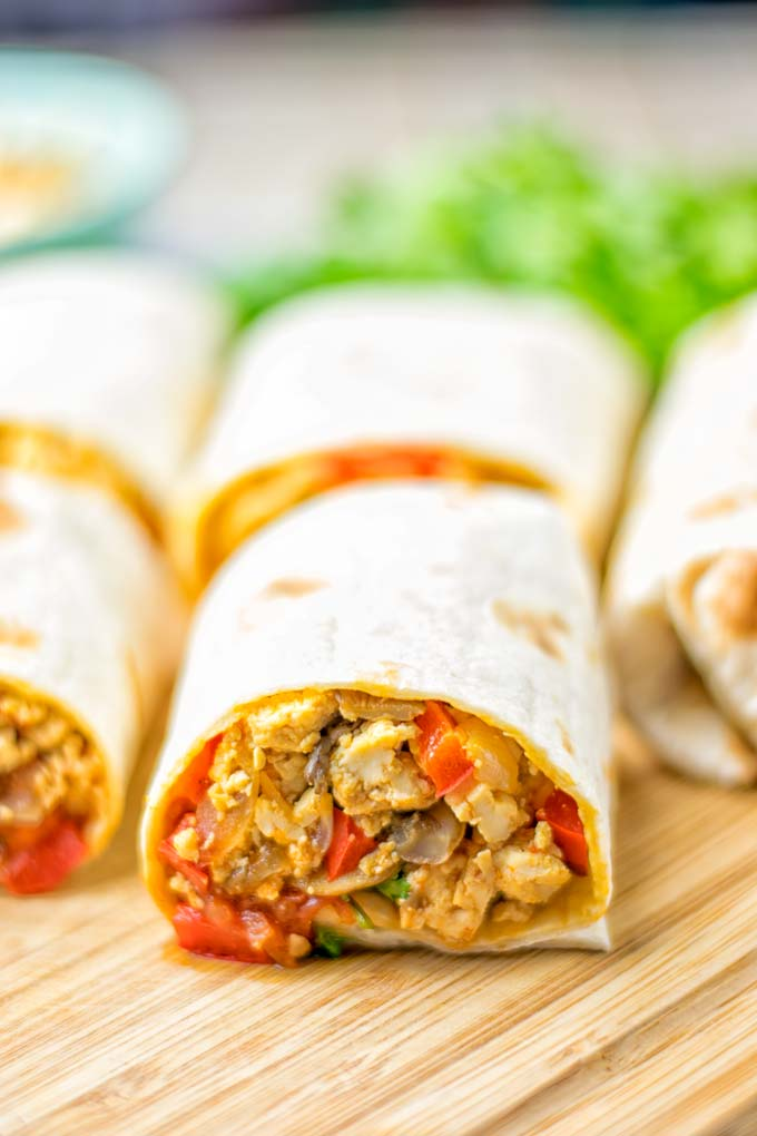 This Vegan Breakfast Burrito with Tofu Scramble is super easy to make and seriously the best burritos you've ever made and tasted. No one would guess it's entirely vegan, gluten free and your family won't miss the cheese or meat in these. These are also an amazing pick for meal prep, dinner, lunch, work lunch and so much more. #vegan #dairyfree #glutenfree #contentednesscooking #breakfastburritos #tofuscramble #breakfastideas #budgetmeals #dinner #lunch #mealprep #worklunchideas
