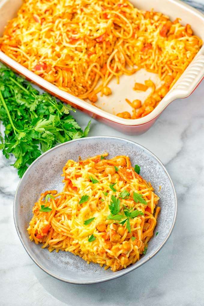 Vegan Spaghetti casserole portion dressed with parsley. Background red casserole dish.