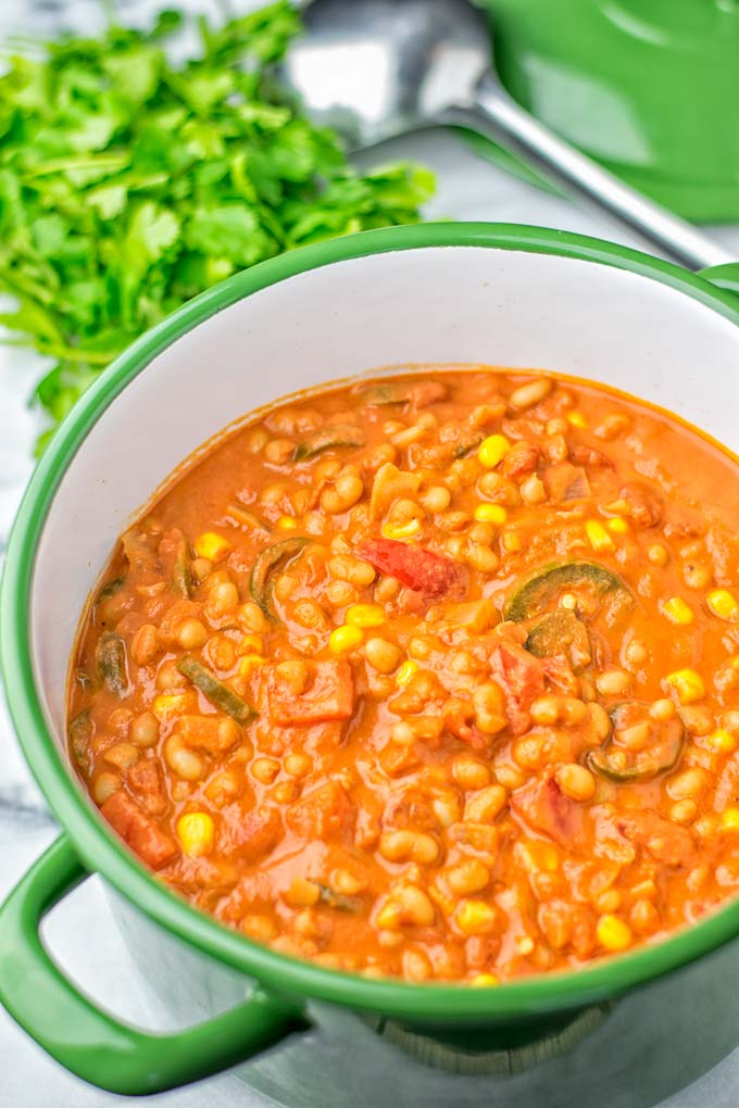Ingredients of the vegetarian white bean chili visible in pot.