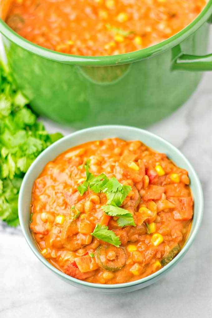 Bowl with the white bean chili decorated with cilantro.
