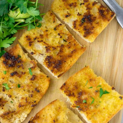 Top view of a plate with slices of Garlic Bread.
