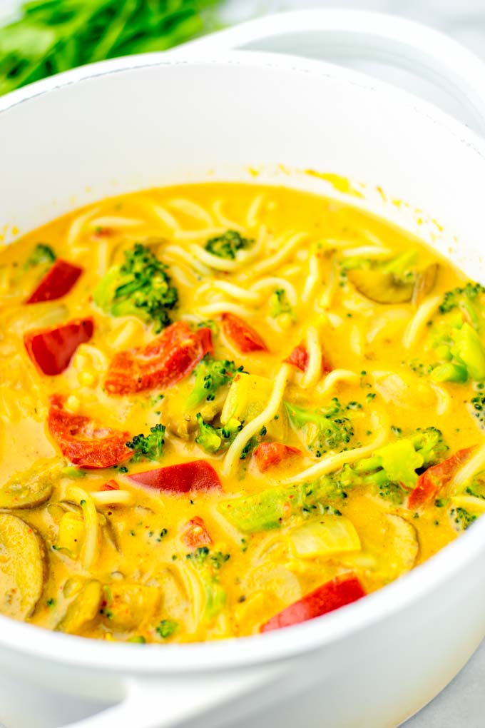 Closeup of coconut curry noodle soup, showing vegetables.