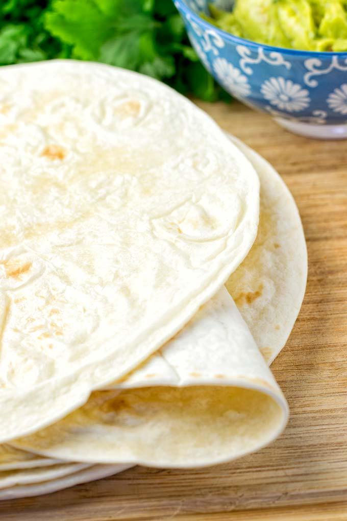Freshly baked tortillas on a wooden board.