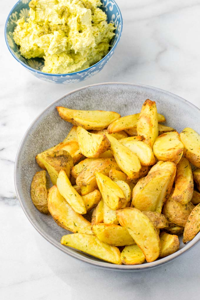 A bowlful of potato wedges in front of the ready pesto butter.