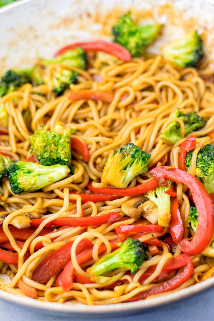 Broccoli florets and thin bell pepper slices with wok noodles.
