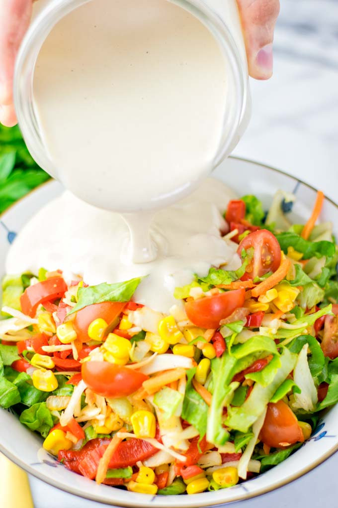 Tahini Dressing is poured from the jar onto a fresh salad.