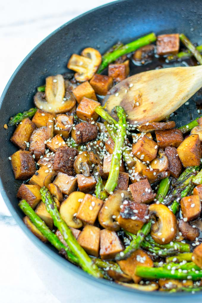 Topping the Stir Fry with extra sesame seeds.