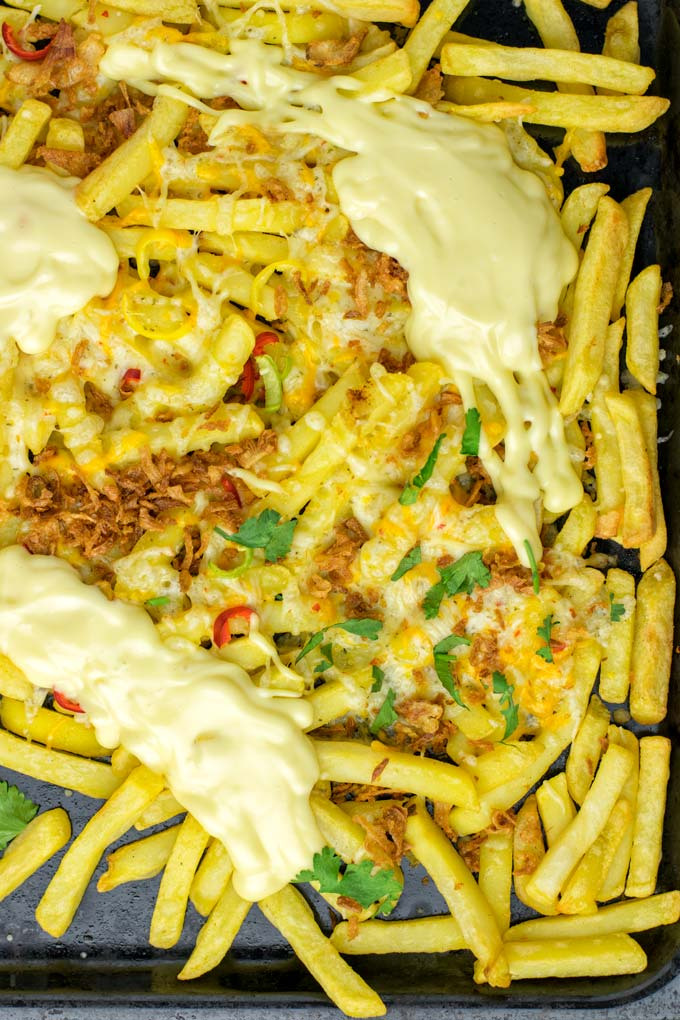 Animal Style Fries are loaded with cheese and roasted onions, topped with satay sauce and optionally cilantro.