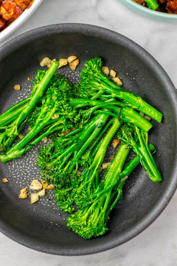 Broccoli is roasted with a touch of oil in a pan, seasoned with salt, pepper, and garlic slices.
