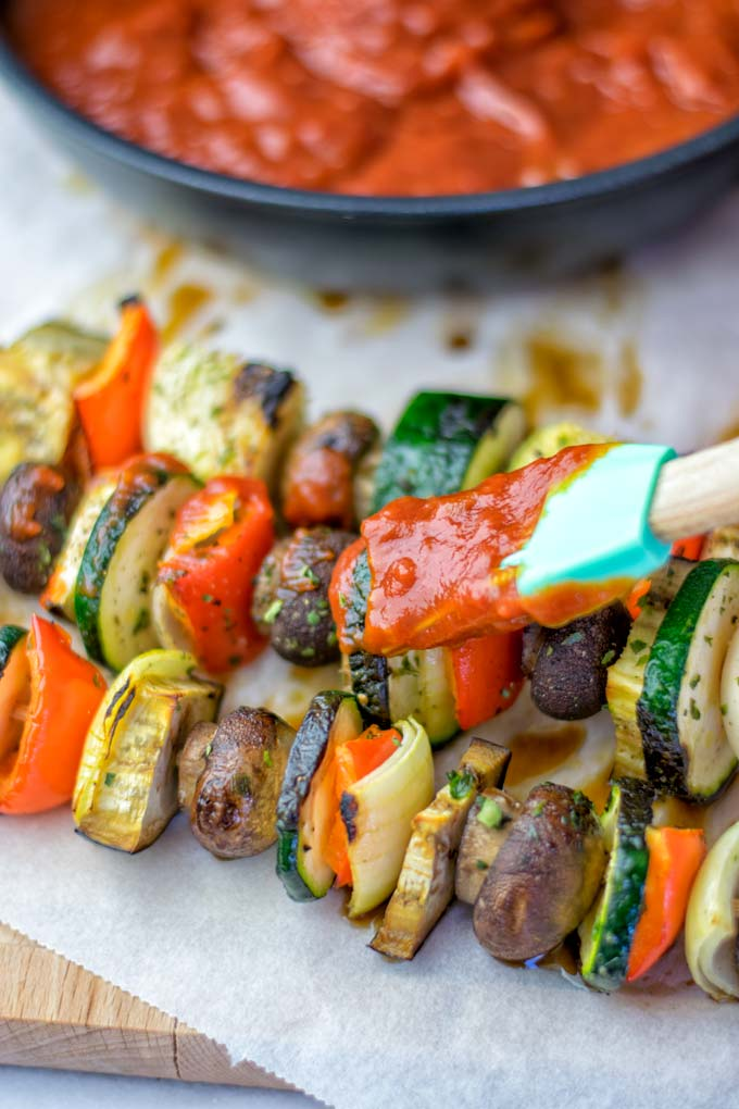 Coating veggie skewers with the Sugar Free BBQ sauce.