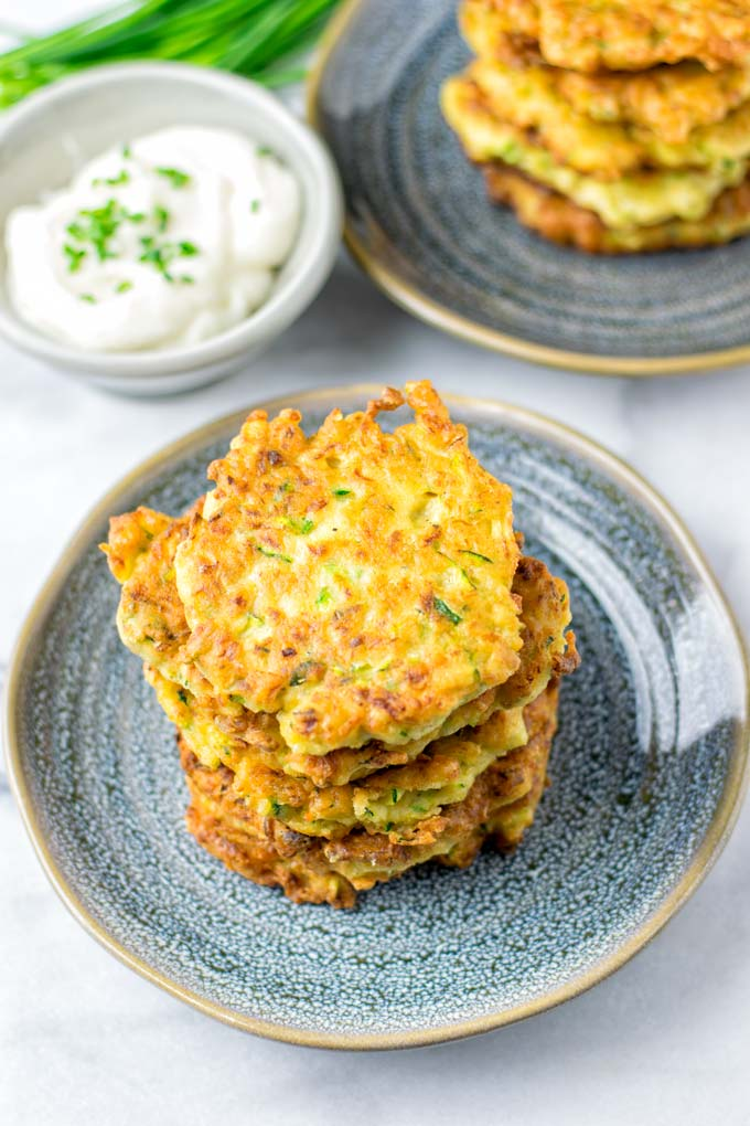 Stack of Zucchini Fritters on a blue plate with a small bowl of dip in the background.