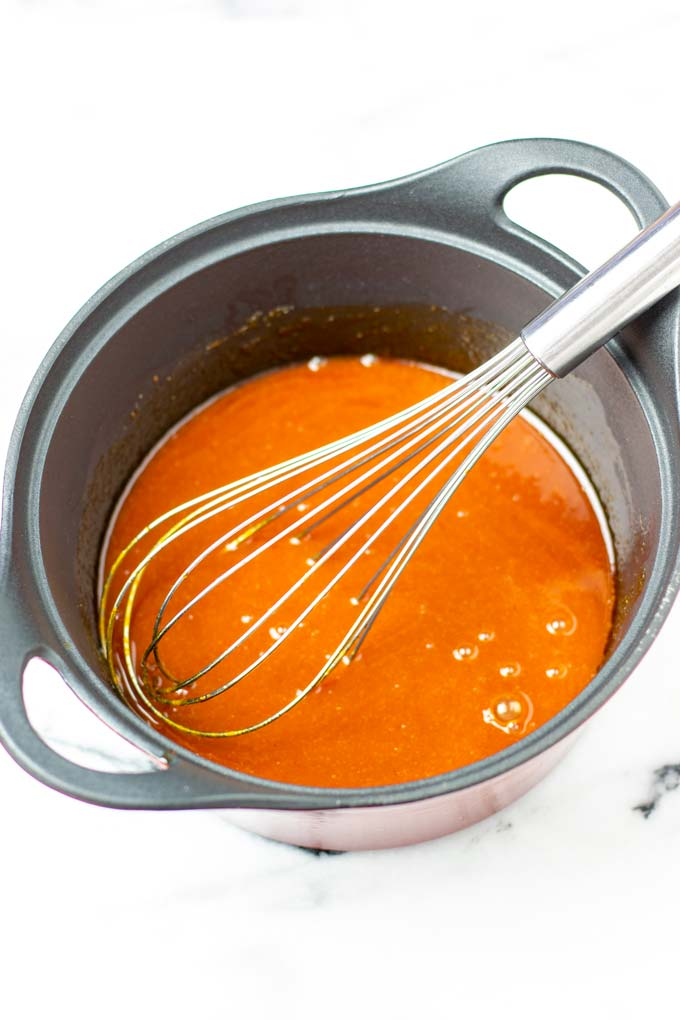 Closeup on Wing Sauce in a saucepan with wire whisk.