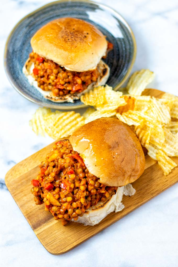 Sloppy Joes with buns on a serving board and plate, served with potato chips.