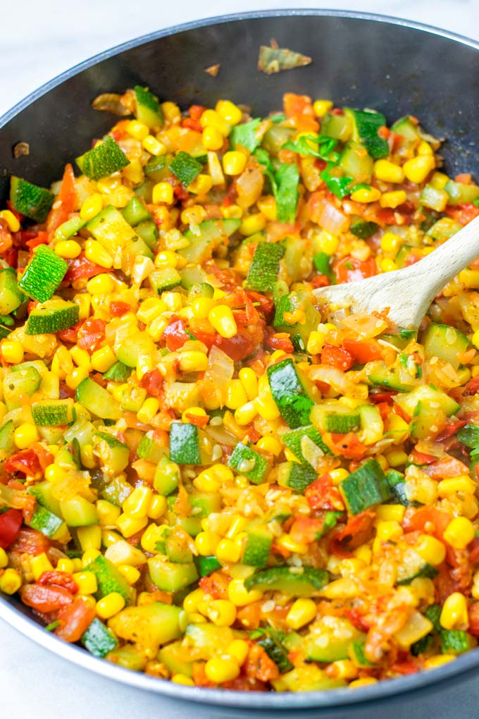 Wooden spoon in a pan with Calabacitas.