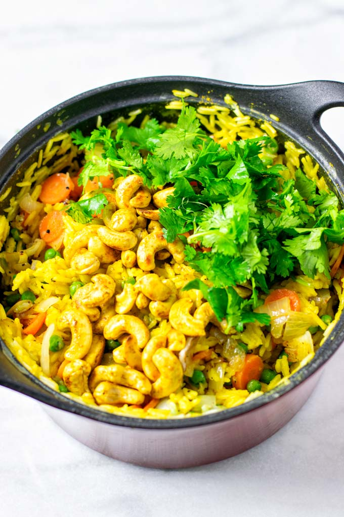 Fresh cilantro is used to garnish the Curried Rice in a large pot.