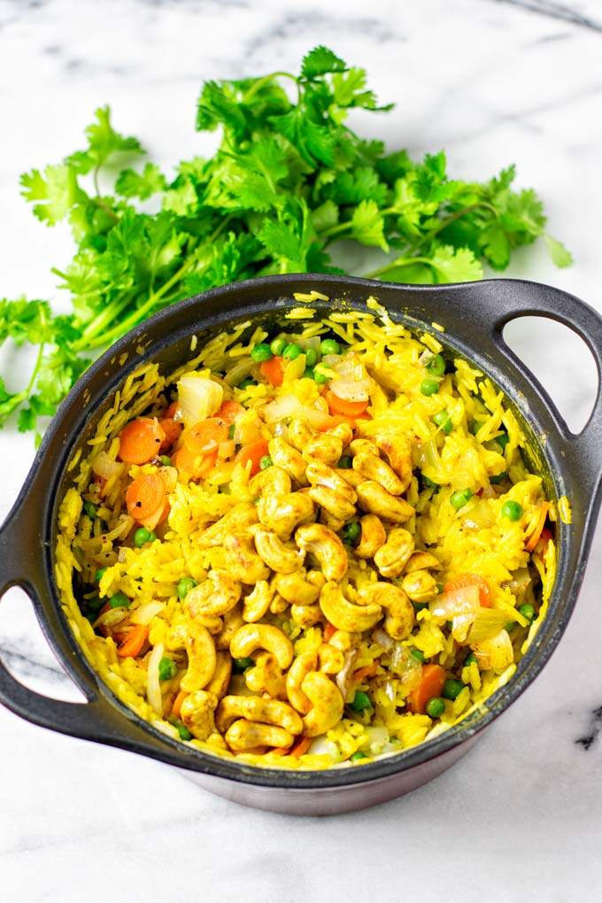 The Curried Rice is finished in a sauce pan, with some fresh cilantro in the background.