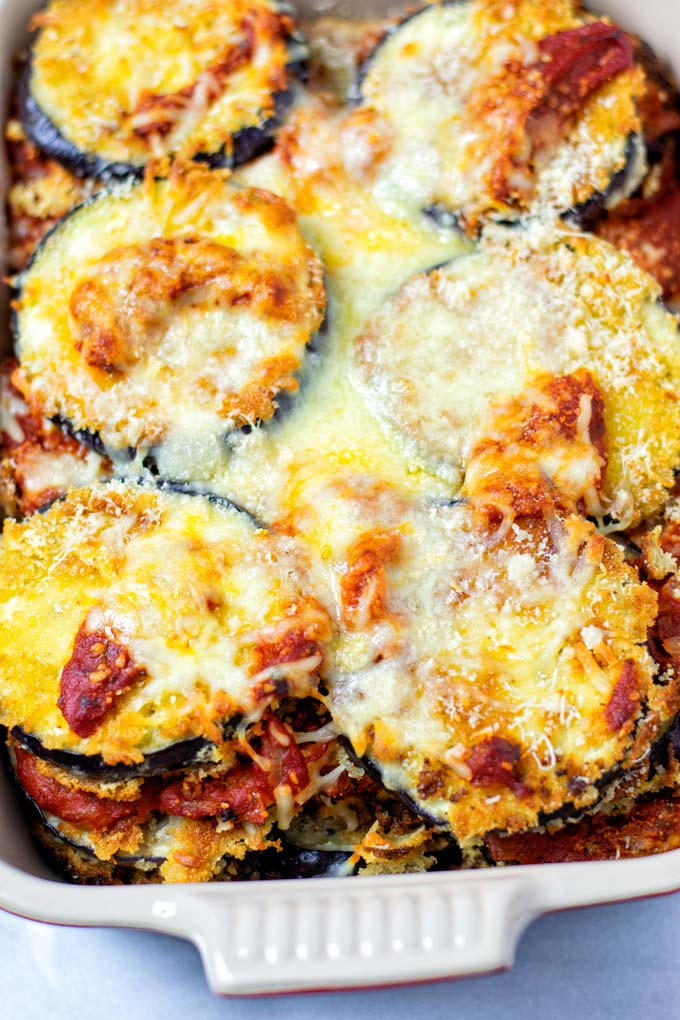 Closeup view on the Eggplant Parmesan showing the baked layers of eggplant, tomato sauce, and cheeses.