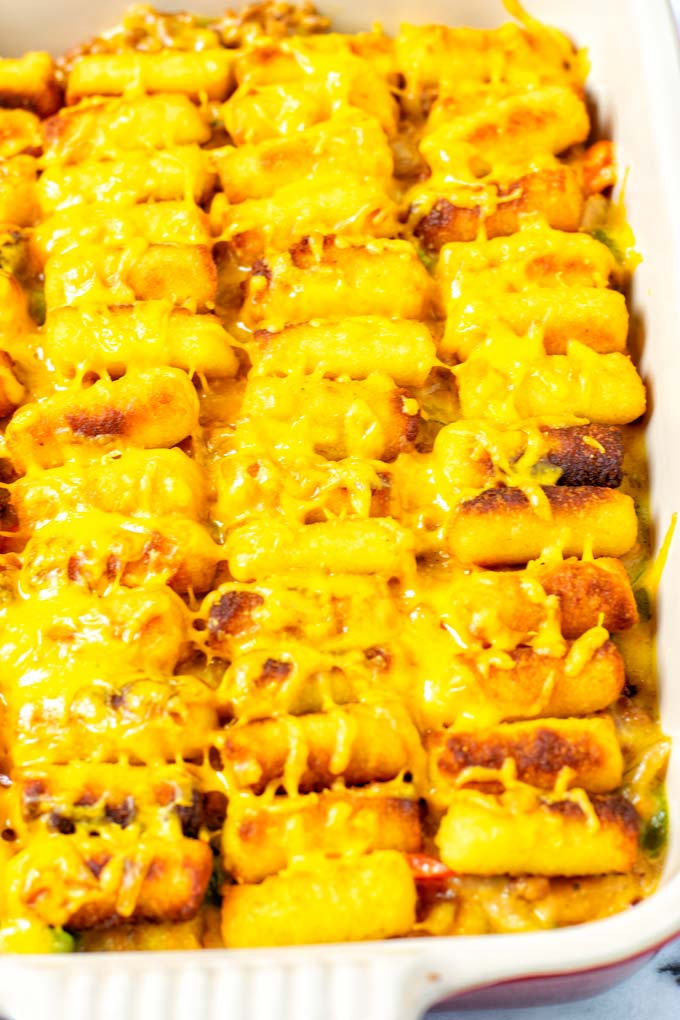 Closeup of the Tater Tot Casserole after baking, with melted vegan cheddar on top.