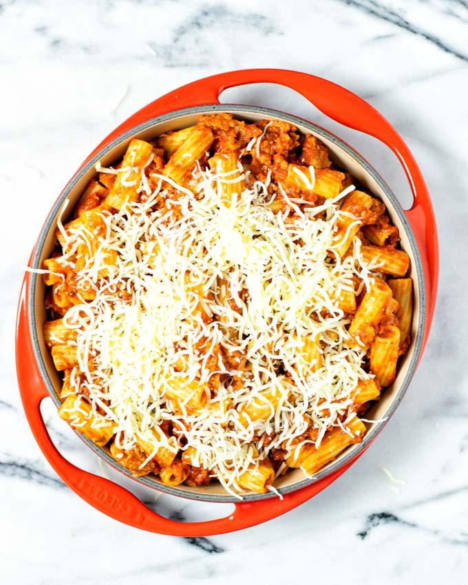 Vegan mozzarella shreds are given over the pasta in the casserole dish.