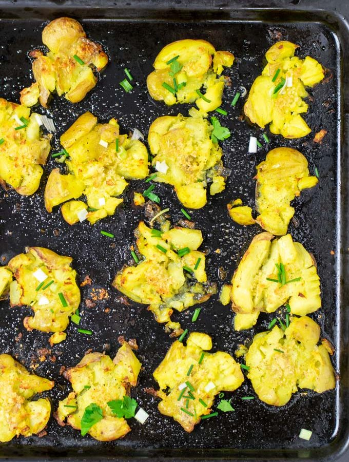 Smashed Potatoes on a bkaing sheet after baking, garnished with some fresh herbs.