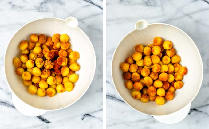 Toasted tater tots are mixed with hot spice mixture in a large mixing bowl.