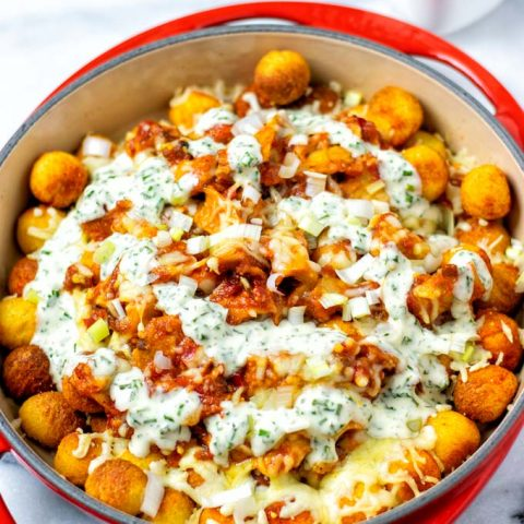 The casserole dish with the Totchos covered with Ranch Dressing.