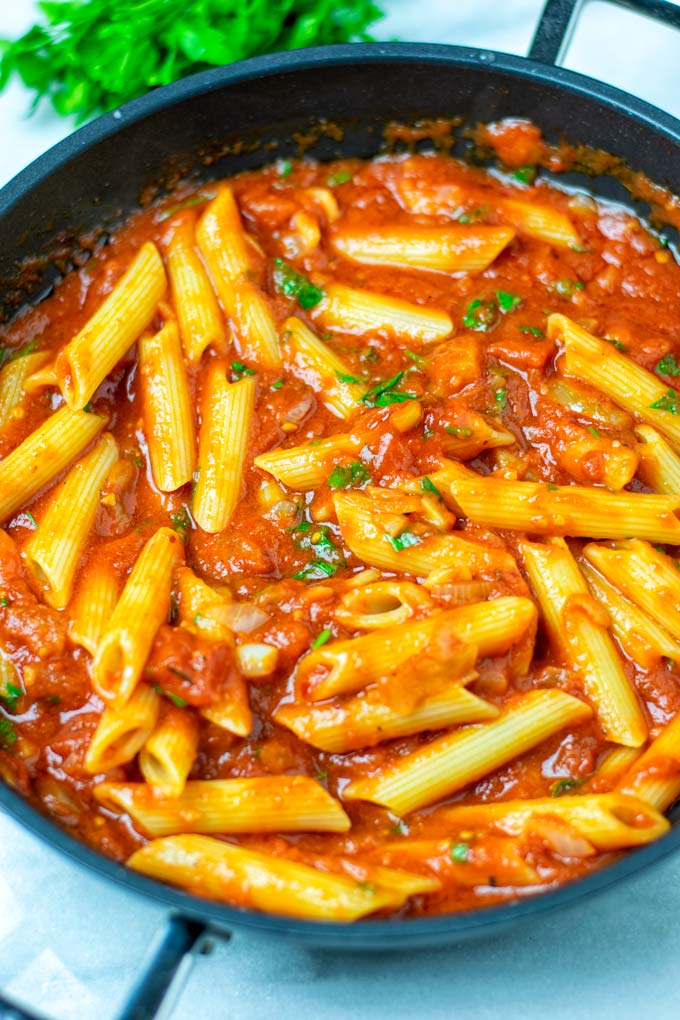 Cooked pasta is mixed with the Arrabbiata Sauce in the saucepan.