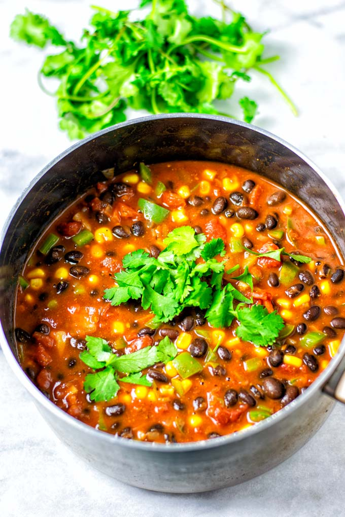 The Black Bean Chili is served in a large saucepan with some fresh cilantro on top.