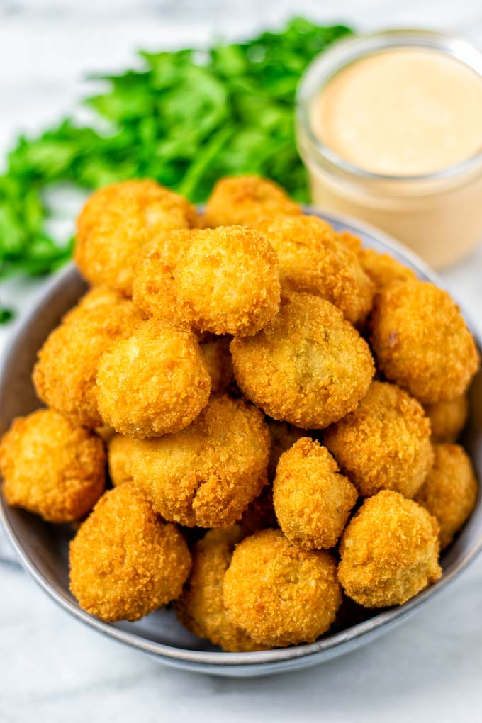 Large bowl full of ready Fried Mushrooms, with golden brown crust and a dipping sauce in the background.